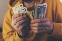 Casual man is counting american dollar banknotes stock image