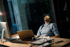 Tired man sleeping in office. Casual man covering eyes with colorful stickers and sleeping at desk in office Stock Photos