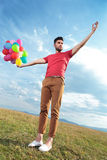 Casual man creates illusion of holding balloons Stock Photos