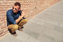 Casual man crouches by brick wall Stock Images