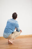 Casual man crouching on floor looking at wall. At home in the living room Stock Photo