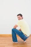 Casual man crouching on floor looking at wall at home. In the living room Royalty Free Stock Photos