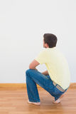 Casual man crouching on floor looking at wall at home. In the living room Stock Image