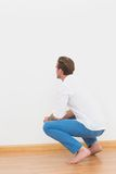 Casual man crouching on floor looking at wall Stock Photo