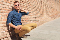 Casual man crouching by wall & smiling Stock Photo