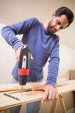Casual man drilling hole in plank Stock Photo