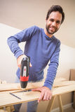 Casual man drilling hole in plank Royalty Free Stock Photos