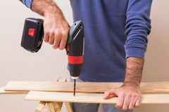 Casual man drilling hole in plank Stock Photography