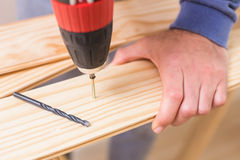Casual man drilling hole in plank Stock Image