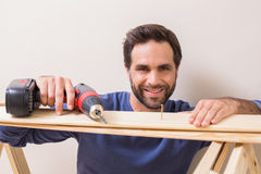 Casual man drilling nail in plank Royalty Free Stock Photos