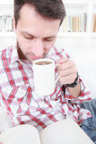 Casual man drinking coffee or tea and reading book Stock Images