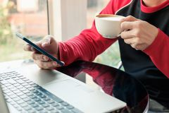 Casual man drinking coffee with using smartphone with laptop in. Cafe Stock Photos