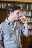 Casual man drinking water in library. Young man in shirt drinking water from crystal glass on background of bookshelves Royalty Free Stock Photo
