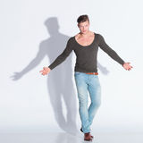 Casual man extends his arms in rage. Full body picture of a casual young man extending his arms while looking at the camera with rage. on gray studio background Royalty Free Stock Image