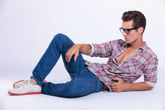 Casual man on the floor looking away Royalty Free Stock Images