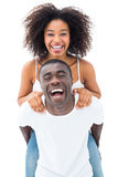 Casual man giving his smiling girlfriend a piggy back Stock Images