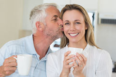 Casual man giving his smiling partner a kiss on the cheek Royalty Free Stock Images