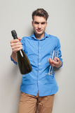 Casual man giving you a bottle of champagne Royalty Free Stock Images