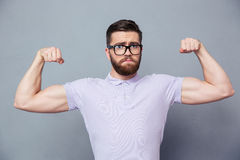 Casual man in glasses showing his biceps Stock Photo