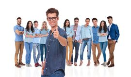 Casual man with glasses with team behind makes ok sign. Casual men wearing glasses with young team behind makes ok sign while standing on white background with a stock image
