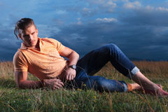Casual man in the grass looking at you Stock Photography
