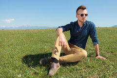 Casual man in the grass looks away Stock Photo