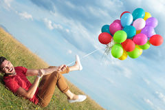 Casual man on the ground pulled by balloons Stock Photo