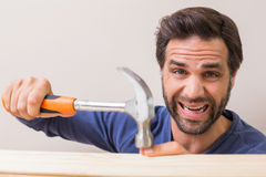 Casual man hammering his finger by accident Royalty Free Stock Photo