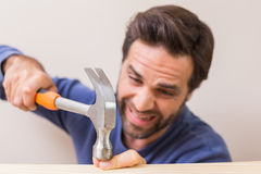 Casual man hammering his finger by accident Stock Photo
