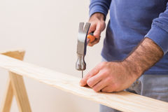 Casual man hammering nail in plank Royalty Free Stock Photos