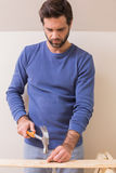 Casual man hammering nail in plank Royalty Free Stock Image
