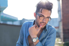Casual man with hand on lip Stock Photos