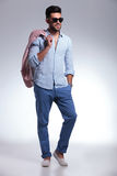 Casual man with hand in pocket and jacket on shoulder royalty free stock images