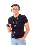 Casual man with hand in pocket listening to music on headphones Royalty Free Stock Photography