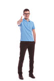 Casual man with hand in pocket shows ok sign. Full length picture of a young casual man showing the thumb up gesture while holding a hand in his pocket. on white Stock Photo