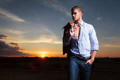 Casual man with hand in pocket at sunset looks away Stock Images