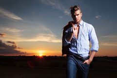 Casual man with hand in pocket at sunset. Casual young man standing with a hand in his pocket outdoor during sunset Royalty Free Stock Photo
