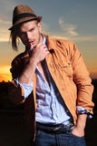 Casual man with hand in pocket and thumb on lip at sunset Stock Image