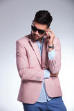 Casual man with hand on sunglasses looks down Royalty Free Stock Photography