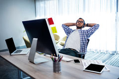 Casual man with hands behind hand resting at desk Royalty Free Stock Photo