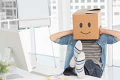 Casual man with happy smiley box over face at office. Casual young man with happy smiley box over face while sitting on chair at office stock photos