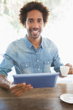Casual man having coffee while using tablet. At the coffee shop stock image