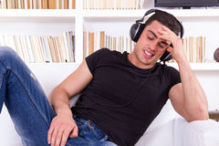 Casual man with headphones relaxing on the sofa at his home Stock Photography