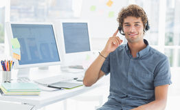 Casual man with headset sitting by computers in office Stock Photos