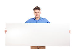 Casual man hold a empty banner in his hands. Stock Photo