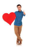 Casual man holding big heart and making the ok sign Stock Photography