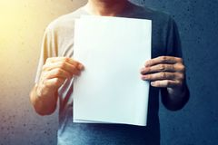 Casual man holding blank A4 paper as copy space. Casual man holding blank A4 paper as mock up copy space for text or graphic design Stock Photo