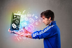 Casual man holding laptop with colorful hand drawn multimedia sy Royalty Free Stock Image