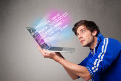 Casual man holding laptop with exploding data and numbers Royalty Free Stock Image