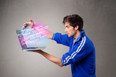 Casual man holding laptop with exploding data and numbers Royalty Free Stock Images
